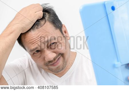 A Middle-aged Man Shines In The Mirror And Worry About Hair Loss Or Hair Gray  Isolated An White Bac