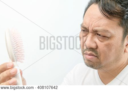 Middle-aged Man Looking At Comb Brush With Loss Hair And Stressed About His Hair Loss Problems Isola
