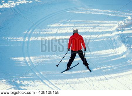 Female Cross Country Skier In A Slope Through The Forest On A Sunny Winters Day.