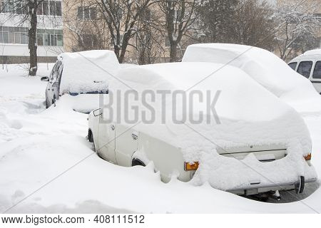Parked Cars, Covered In Snow, Stand Along The Road, Selective Focus. Snowfall In The City, Falling S