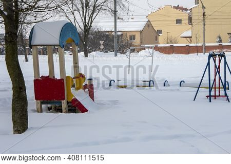 Open City Playground Covered With Snow In Winter. Concept: Snow Drifts, The Work Of The Rescue Servi