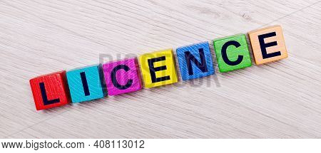 On A Light Wooden Background On Multi-colored Bright Wooden Cubes The Word Licence