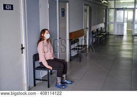 Woman In Face Mask Sits In The Hallway Of An Empty Clinic Without People And Patients. Clinic Recove