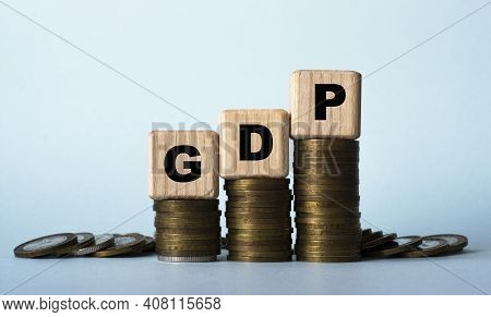 Gdp (gross Domestic Product) - Acronym On Wooden Cubes. Which Stand On Stacks Of Coins On A Light Ba