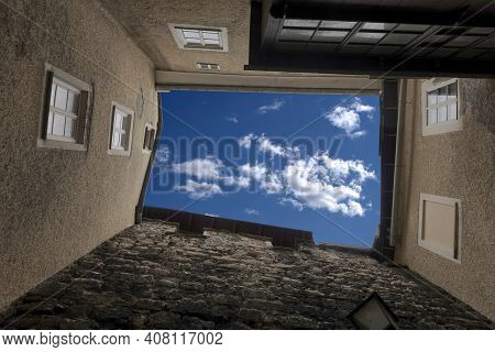 Bottom Up View To Blue Sky With White Clouds From Dense Standing Buildings In The Typical West Europ