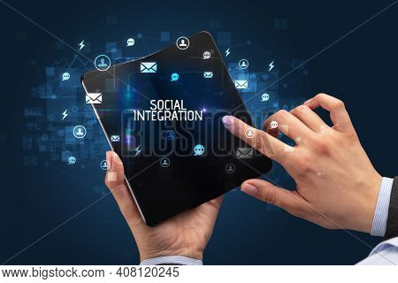 Businessman holding a foldable smartphone with SOCIAL INTEGRATION inscription, social networking concept