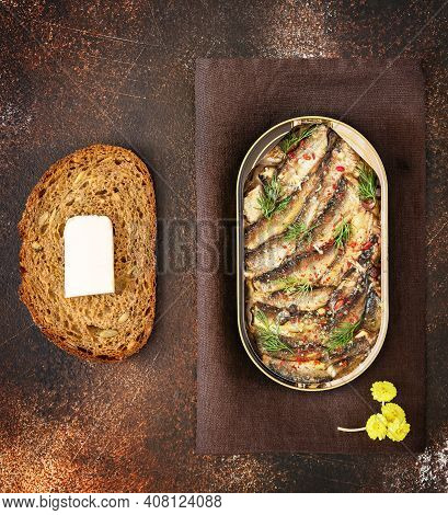 Open Tin Of Baltic Sprats In Oil With Spices, A Slace Of Bread With Butter On An Old Brown Backgroun