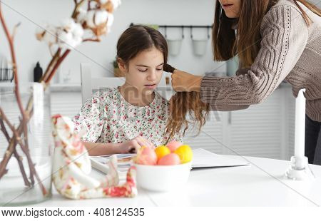 1 White Teen Girl 10 Years Old Sits At The Kitchen Table, Mom Braids Her Pigtail, Easter Eggs