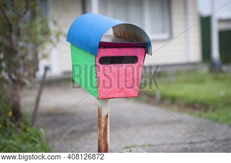Old Simple Metal Mailbox In Quirky Colors Of Blue, Green And Pink