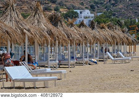 Ios, Greece - August 1, 2019 : Sunbeds And Umbrellas On The Sandy Beach Of Mylopotas In Ios Cyclades
