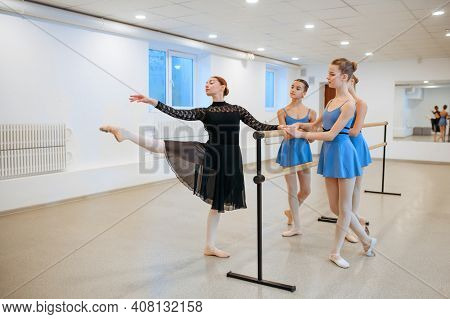 Master and ballerinas, exercise at barre in class