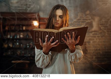 Young demonic woman holds book of spells