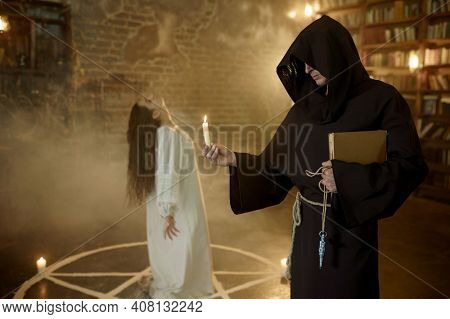 Exorcist in hood casting out demons from a woman