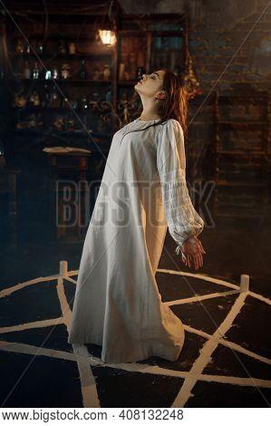 Creepy demonic woman standing in the magic circle
