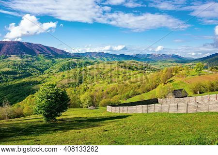 Mountainous Rural Landscape In Spring. Green Fields, Pastures And Trees On The Hills Rolling In To T