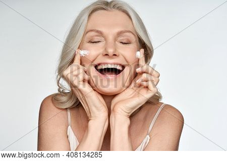 Happy Funny 50s Middle Aged Mature Old Blond Woman Applying Facial Cream On Face Laughing Enjoying S