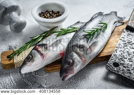 Raw Seabass Fish On A Cutting Board With , Herbs. White Background. Top View
