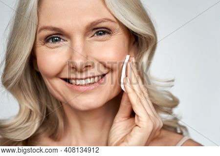 Smiling 50s Middle Aged Older Woman Holding Cotton Pad Sponge Cleansing Face Skin With Cleanser, Hap