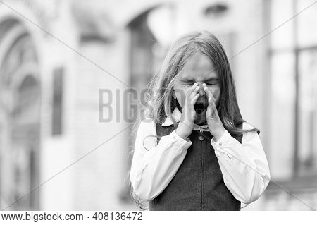 Small Kid With Blond Hair Wearing School Uniform Give Long Yawns In Schoolyard, Morning.