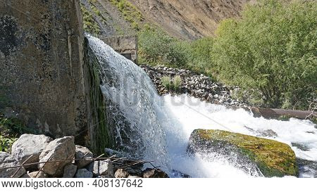 Draining The Water Pressure Into The River. The Water Flows Like A Waterfall And Flows Into The Rive