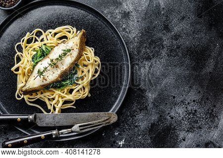 Baked Halibut Fish Steak And Spaghetti Pasta With Spinach. Black Background. Top View. Copy Space