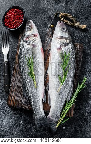 Raw Seabass Fish On A Cutting Board With , Herbs. Black Background. Top View