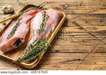 Whole Raw Red Perch Or Sea Bass Fish On A Plate. Wooden Background. Top View. Copy Space