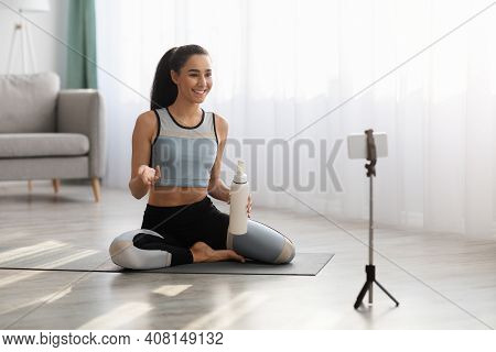 Young Woman In Sportswear Fitness Trainer Sitting On Yoga Mat, Holding Bottle Of Water, Broadcasting