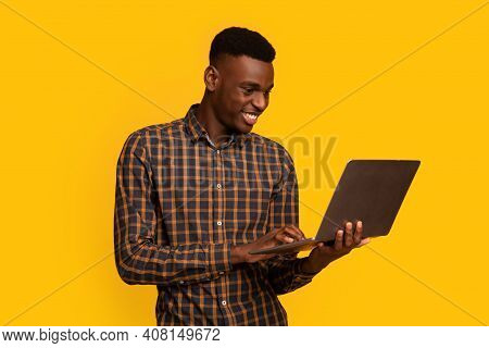 Freelance Work. Portrait Of Smiling African American Guy Using Laptop While Standing Isolated Over Y