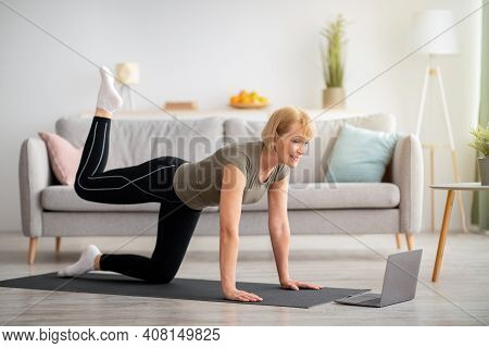 Online Home Fitness Concept. Beautiful Mature Woman Exercising To Sports Video On Laptop In Living R