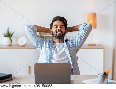 Smiling Arab Freelancer Guy Leaning In Chair, Relaxing At Workplace After Working Remotely On Laptop