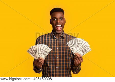 Big Luck. Excited Black Millennial Guy Holding Lots Of Dolar Cash And Exclaiming With Excitement, Jo