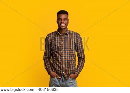 Portrait Of Young Handsome Black Guy In Checkered Shirt Over Yellow Background, Cheerful Millennial