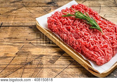 Fresh Raw Mince Beef, Ground Meat On Butcher Paper. Wooden Background. Top View. Copy Space