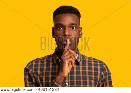 Its A Secret. Young Black Guy Making Shh Silence Gesture, Mysterious African Man Putting Finger On L