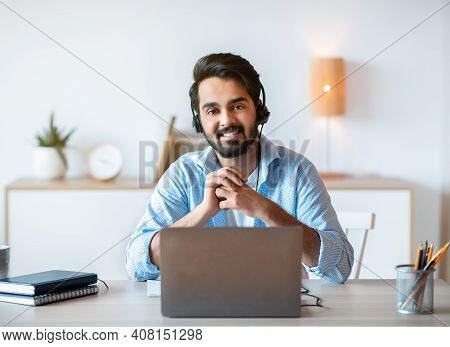 Remote Job Opportunities. Portrait Of Smiling Arab Man Hotline Manager In Headset Posing At Workplac