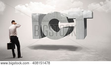 Rear view of a businessman standing in front of ICT abbreviation, modern technology concept