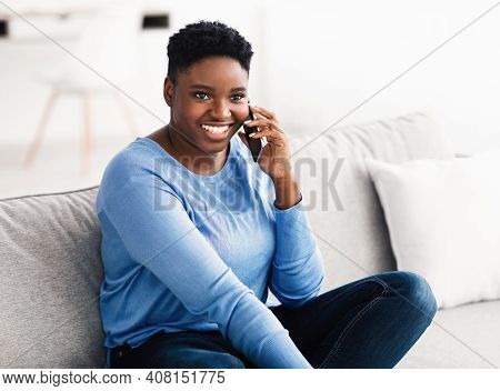 Happy Cheerful Young Black Woman Talking On The Phone At Home, Smiling Lady Making Call By Cellphone