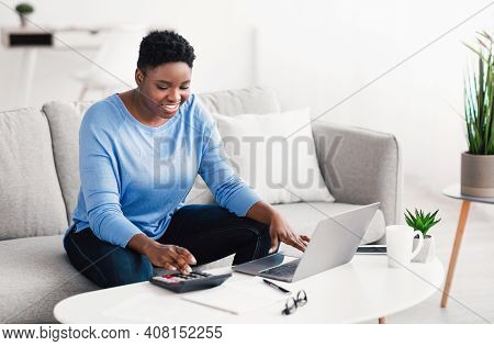 Business Concept. Smiling African American Female Accounting Analyst Calculating Income And Expenses