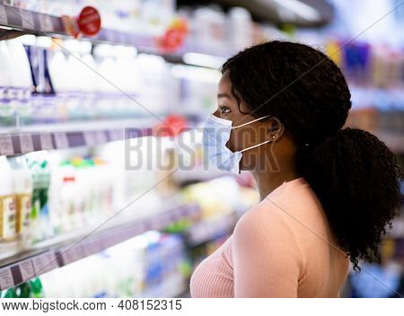 Side View Of Black Lady In Face Mask Choosing Dairy Products At Modern Supermarket During Covid-19 L