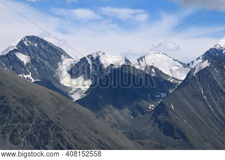 Rocky High Mountain Peaks With Glacier And Snow In The Altai Mountains On The Background Of The Sky