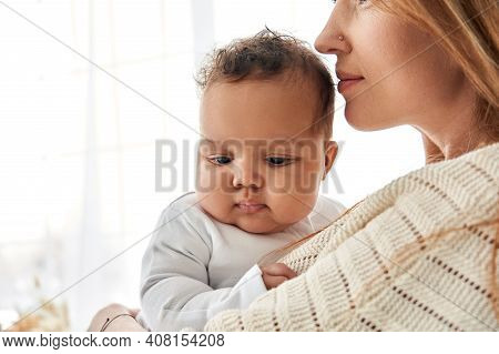 Young Caucasian Mum Hugging Cute Adorable Infant African American Baby Daughter Expressing Single Pa