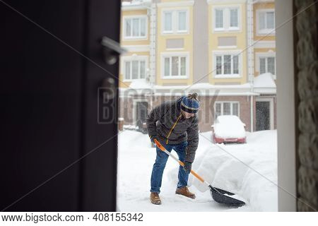 A Mature Man Clean Path Near House From Snow During Strong Blizzard. Person Shoveling Snow Out Of Th