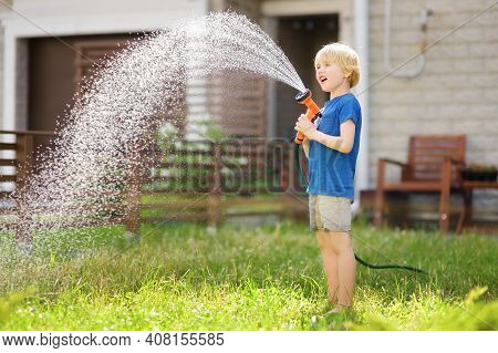 Little Boy Watering Lawn And Playing With Garden Hose With Sprinkler In Sunny Backyard. Preschooler