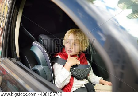 Little Boy Is Sitting In The Front Seat Of Car. Child Travels With Single Parent. Safety Of Transpor