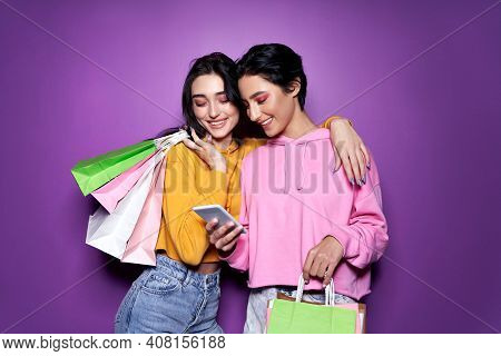 Two Happy Women Friends Shoppers Holding Shopping Bags Using Mobile Apps For Online Shopping Standin