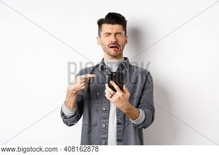Sad Crying Guy Pointing At Smartphone And Sobbing, Complaining Or Feeling Miserable, Standing On Whi