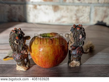 Big Red Apple And Funny Trolls Figures On The Wooden Table Against The Brick Wall