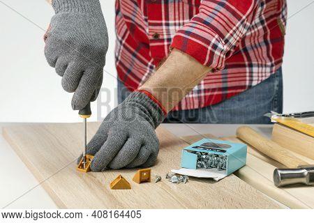 Man Fixing A Furniture Fitting On Board At Home With A Screwdriver. Caucasian Man Assembling Furnitu