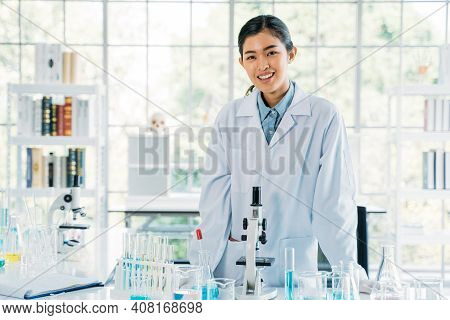 Portrait Of Successful And Beautiful Young Female Asian Medical Researcher And Scientist Wearing Lab